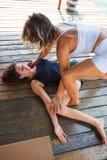 Istruttore di forma fisica che assiste giovane donna nell'allungamento dell'esercizio Immagine Stock Libera da Diritti
