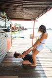 Istruttore di forma fisica che assiste giovane donna nell'allungamento dell'esercizio Fotografie Stock Libere da Diritti