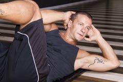 Istruttore di forma fisica che fa sit-ups Immagini Stock