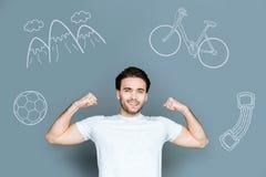 Istruttore di forma fisica che sorride e che mostra i suoi muscoli immagini stock