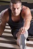 Istruttore di forma fisica che streching il suo piedino Immagine Stock