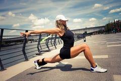 Istruttore di forma fisica della donna che fa il promenad della città di giorno di estate di addestramento Fotografia Stock