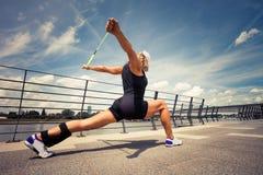 Istruttore di forma fisica della donna che fa il promenad della città di giorno di estate di addestramento Immagini Stock Libere da Diritti