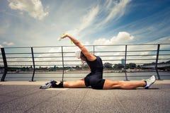 Istruttore di forma fisica della donna che fa il promenad della città di giorno di estate di addestramento Immagini Stock