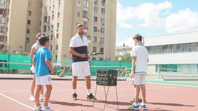 Istruttore di tennis professionale che mostra articolo sportivo ai bambini all'aperto video d archivio