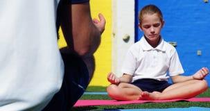 Istruttore di yoga che istruisce i bambini nell'esecuzione dell'yoga archivi video