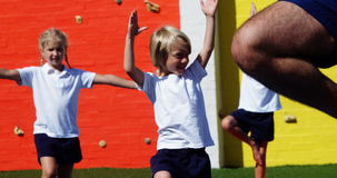 Istruttore di yoga che istruisce i bambini nell'esercitarsi stock footage