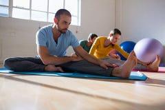 Istruttore di yoga con gli studenti che allungano le gambe al club Immagine Stock