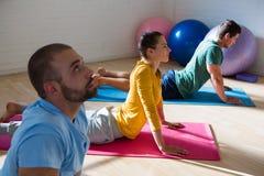 Istruttore di yoga con gli studenti che praticano posa della cobra in club Immagini Stock