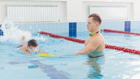 Istruttore e bambino che fanno gli esercizi nella piscina La vettura insegna al ragazzo a nuotare stock footage