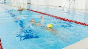 Istruttore e bambino che fanno gli esercizi nella piscina La vettura insegna alla ragazza a nuotare archivi video