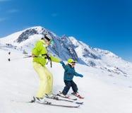 Istruttore e bambino che sciano giù la montagna Fotografie Stock