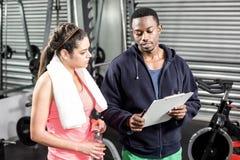 Istruttore e donna che esaminano piano di allenamento Immagine Stock