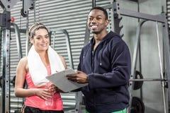 Istruttore e donna che esaminano piano di allenamento Immagini Stock