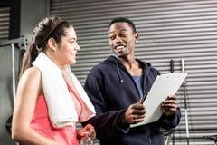 Istruttore e donna che esaminano piano di allenamento Immagine Stock Libera da Diritti