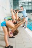 Istruttore e gruppo di bambini che fanno gli esercizi vicino ad una piscina immagine stock
