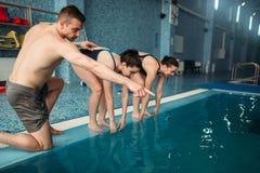 Istruttore e nuotatori femminili nella piscina Fotografie Stock Libere da Diritti