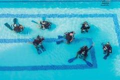Istruttore e studenti di immersione subacquea L'istruttore insegna agli studenti alla d immagine stock