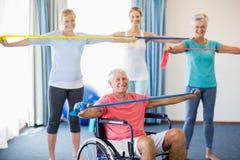 Istruttore ed anziani che si esercitano con l'allungamento delle bande Immagine Stock