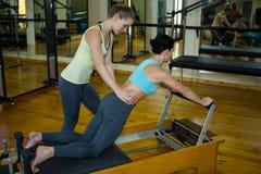Istruttore femminile che assiste donna con l'allungamento dell'esercizio Immagine Stock