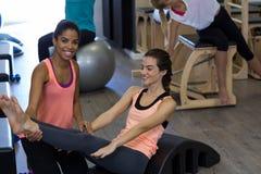 Istruttore femminile che assiste donna con l'allungamento dell'esercizio sul barilotto dell'arco Immagini Stock Libere da Diritti