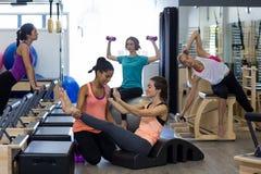 Istruttore femminile che assiste donna con l'allungamento dell'esercizio sul barilotto dell'arco Fotografia Stock