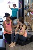 Istruttore femminile che assiste donna con l'allungamento dell'esercizio sul barilotto dell'arco Fotografie Stock Libere da Diritti