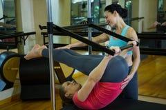 Istruttore femminile che assiste donna con l'allungamento dell'esercizio sul riformatore Fotografia Stock