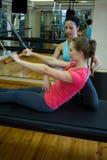 Istruttore femminile che assiste donna con l'allungamento dell'esercizio sul riformatore Fotografie Stock