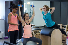 Istruttore femminile che assiste donna con l'allungamento dell'esercizio sulla palla di forma fisica Immagine Stock Libera da Diritti