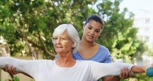 Istruttore femminile che assiste donna senior nell'esercitazione con le teste di legno 4k
