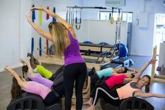 Istruttore femminile che assiste gruppo di donne con l'allungamento dell'esercizio sul barilotto dell'arco Fotografie Stock