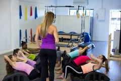 Istruttore femminile che assiste gruppo di donne con l'allungamento dell'esercizio sul barilotto dell'arco Fotografia Stock Libera da Diritti