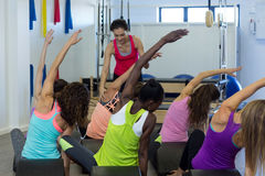 Istruttore femminile che assiste gruppo di donne con l'allungamento dell'esercizio sul barilotto dell'arco Immagini Stock