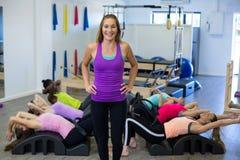 Istruttore femminile che assiste gruppo di donne con l'allungamento dell'esercizio sul barilotto dell'arco Immagine Stock