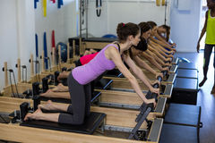Istruttore femminile che assiste gruppo di donne con l'allungamento dell'esercizio sul riformatore Fotografia Stock
