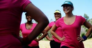 Istruttore femminile che assiste le donne mentre esercitandosi nel campo di addestramento stock footage