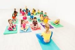 Istruttore femminile che dà la classe di yoga per i bambini Immagini Stock