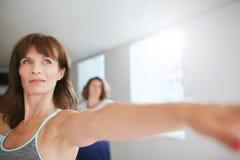 Istruttore femminile che fa allenamento di yoga alla palestra Fotografie Stock
