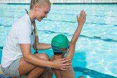 Istruttore femminile che forma un ragazzo per nuotare Fotografia Stock