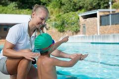 Istruttore femminile che forma un ragazzo per nuotare Fotografie Stock