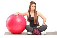 Istruttore femminile di forma fisica che si siede su una stuoia d'esercitazione Fotografia Stock