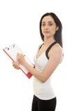 Istruttore femminile di forma fisica con carta Fotografie Stock Libere da Diritti