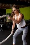 Istruttore femminile di forma fisica con le corde pesanti di forma fisica Immagini Stock