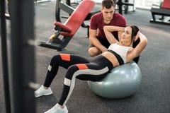 Istruttore Helping Woman di forma fisica nel club di salute Fotografia Stock Libera da Diritti