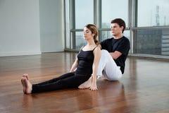 Istruttore Helping Woman With di yoga una posa Immagini Stock Libere da Diritti
