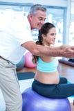 Istruttore maschio che dà esercitando addestramento alla donna incinta Fotografia Stock