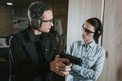 istruttore maschio che descrive pistola al cliente femminile fotografia stock libera da diritti