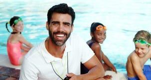 Istruttore maschio che sorride vicino al poolside archivi video