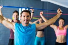 Istruttore maschio con gli atleti nello studio di forma fisica Fotografia Stock